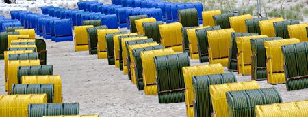 Rows of beach chairs of yellow, black or blue colors at the sand beach of the seaside resort Binmz, Germany