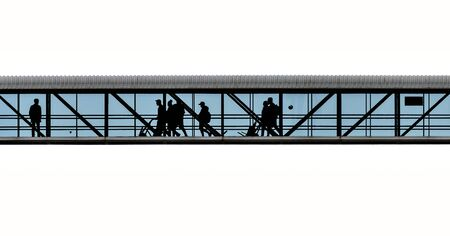 Silhouettes of people on a transparent footbridge at the harbor of Mukran, Germany