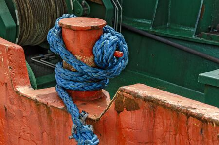 blue rigging looped around an old orange bitt