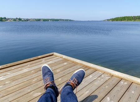 view from a wooden terrace above two blue shoed feet on the blue Baltic sea until the horizon to the archipelago of Västervik, Sweden