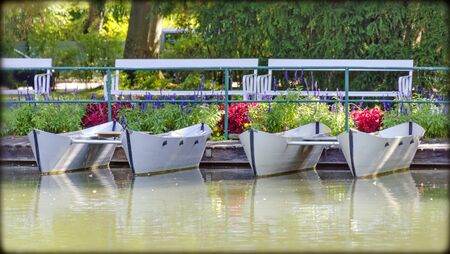 white catamaran boats at the shore of a pond  in the Doblhoffpark at the small town of Baden, Austria
