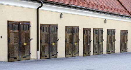 old multiple garaging facility with closed wooden folding doors