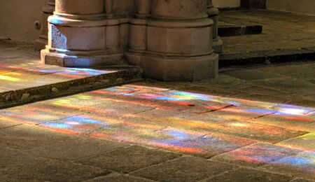 light is falling through colorful windows and producing colorful reflections at the stone floor of a church Reklamní fotografie