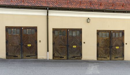 Old multiple garaging facility with three wooden folding doors
