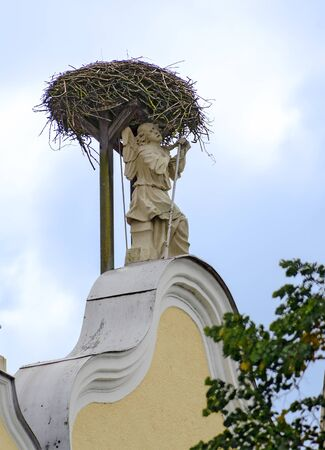 empty nest of a stork above the figure of an angel on a gable of a church