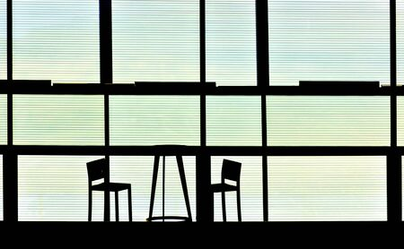 silhouettes of a table and two chairs behind a glass wall with shutter