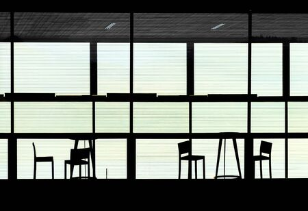 silhouettes of  tables and chairs behind a glass wall with shutter