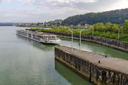 cruising ship entering a lock of the hydraulic power station Ybbs-Persenbeug at the river Danube, Austria