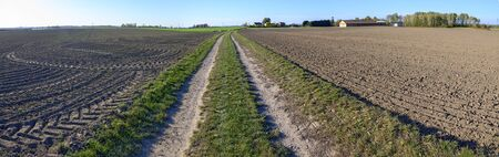 panoramic view of a farmland with path through fresh processed fields with tractor tracks, Austria