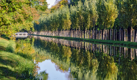 canal with alley trees on a sunny day in autumn in the palace park of Laxenburg, Austria