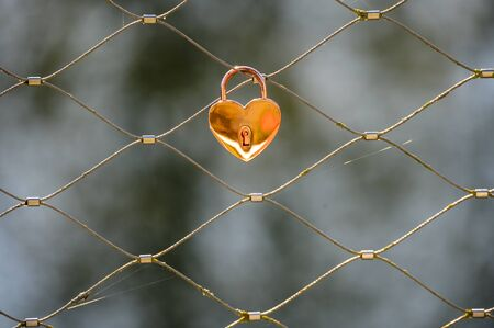 golden padlock shaped like a heart on a mesh made from steel ropes Stock Photo