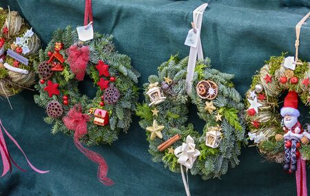 colorful decorated door wreaths for christmas with  brushwood and straw at a market stall Stock Photo
