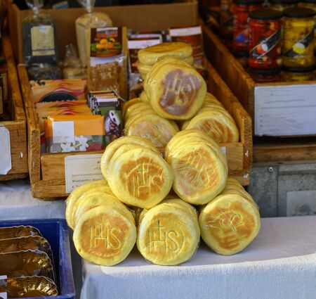 original filled baked pastries from the region Waldviertel (forest quarter) called Mohnzelten ( poppy cakes) with the Christogram IHS at a market stall in Austria