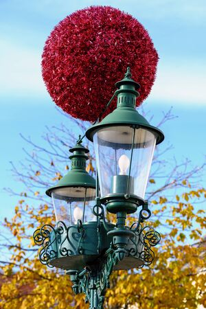 big red glittering ball as christmas decoration on a vintage street lantern in sunshine before blue sky