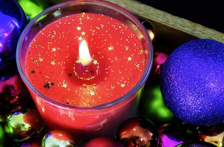 one christmas candle burning and colorful glittering xmas decoration