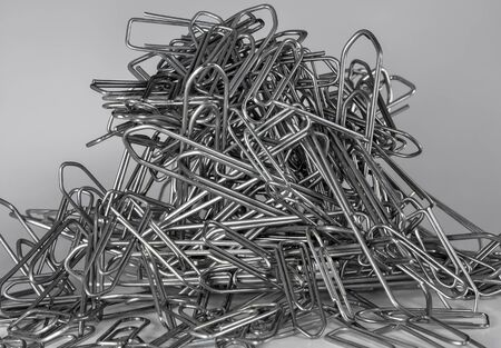 Heap of big and small metallic paperclips Stock Photo