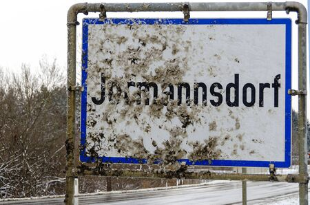 place name sign of the community of Jormannsdorf in the region Burgenland beside a car road partly covered by dirty snow slush, Austria