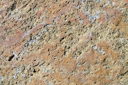 rough surface of a red and brown patterned granite rock