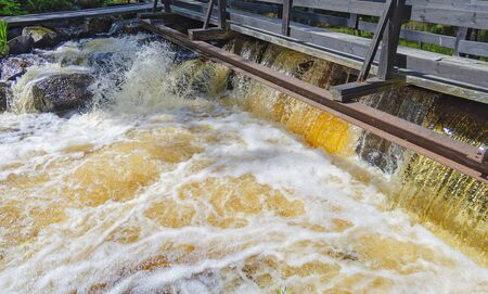 gold coloured water is sparkling, splashing and foaming at an old barrage in Sweden Stock Photo