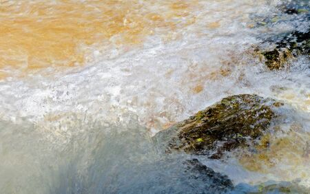 foaming and splashing gold coloured white water overflowing rocks in Sweden Stock Photo