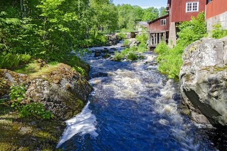 Rapids of a former mill creek in summer in Sweden