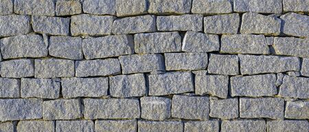 stone wall made from dry piled up broken granite stones