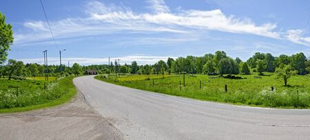 panoramic view of a summerly country landscape with car road in the south of Sweden