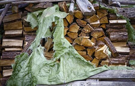 stack of logs of firewood partly covered by a torn sheet Stok Fotoğraf
