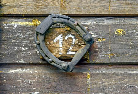 horse shoe on an old wooden wall with the white number twelve