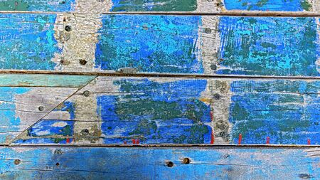 Old weathered wooden boards partially painted in vibrant colours