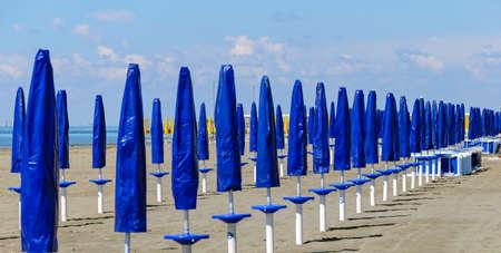 row of sun shades with blue hulls before season on the beach of Grado, Italy