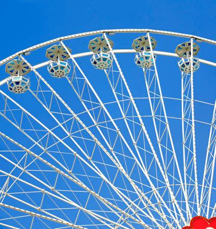 white ferries wheel with gondolas before blue sky Stock Photo