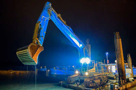 dredger with special shovel for deepen the riverbed in the guest harbor of Tulln on the river Danube at night, Austria
