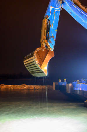 boom of a dredger with special shovel for deepen the riverbed in the guest harbor of Tulln on the river Danube at night, Austria