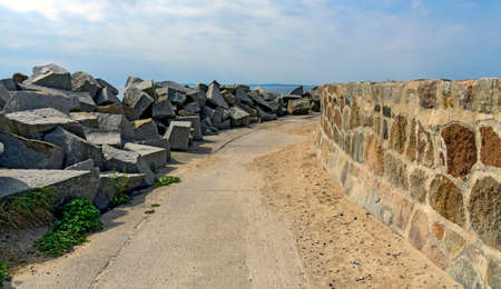 way on a mole between granite blocks as wave breakers and an upright stone wall at the harbor of Sassnitz, Germany