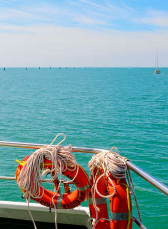 View across the adriatic sea until the horizon with orange lifeboys in the foreground, Italy Standard-Bild