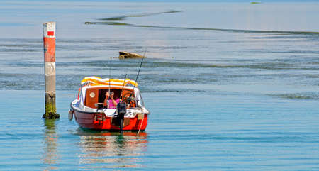 boat of an angler on blue water aside a colorful pole at the lagoon of Grado, Italy
