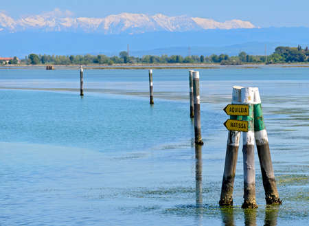 Marking by poles of a route in the lagoon of Grado with snowcovered mountains in the background, Italy Standard-Bild