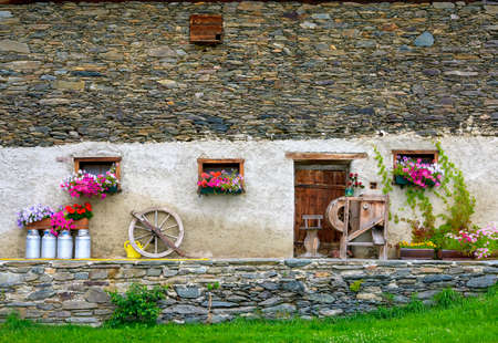front of an old farmhouse with decoration made by flowers and rural things in Austria Standard-Bild