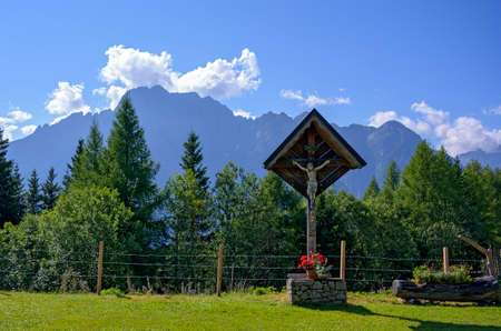 wayside cross on the Star alp above the town of Lienz with the Dolomites in the background, Austria