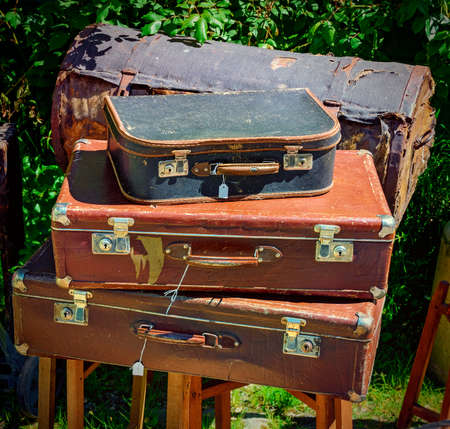 stack of old and desolate suitcases at sunshine, Sweden Standard-Bild