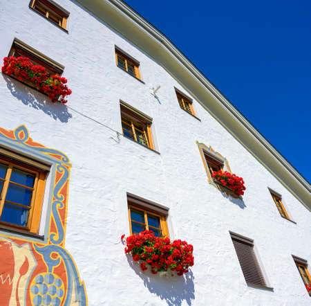white front of a house with red flower decoration before blue sky, Austria