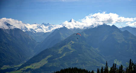 View from the mountain Schmittenhoehe onto the panorama of the partly snowcovered peaks of the High Tauern with Kitzsteinhorn and Glockner group in the region of Pinzgau and a red paraglider, Austria