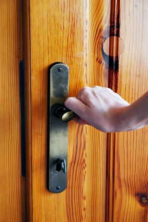 door knob: Hand opening the wooden door