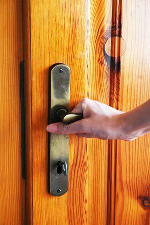 door knob: Hand opening the wooden door