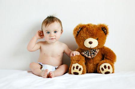 Little boy sitting next to a teddy bear Stock Photo