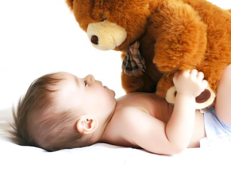 Little boy playing with a bear photo