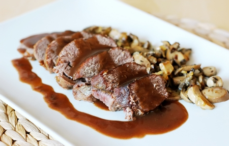 Venison with wine rose sauce and mushrooms photo