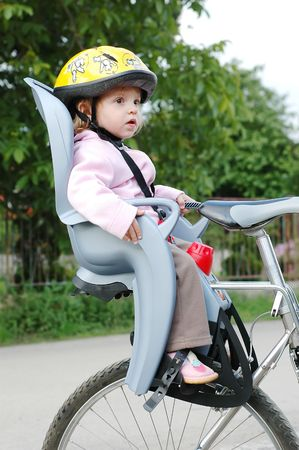 helmet seat: Little girl in the seat bicycle with a helmet on his head