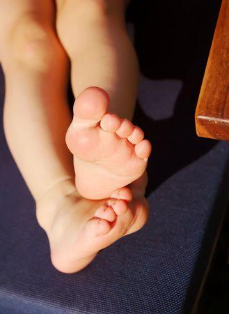 A childrens feet on a blue deckchair. photo